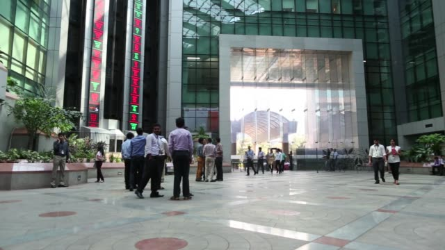 employees walk past electronic boards displaying stock figures in the atrium of the national stock exchange of india ltd building in mumbai india on... - paris stock exchange stock videos & royalty-free footage