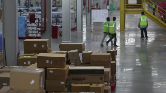 Employees walk past stacked palettes in the warehouse at the Amazoncom Inc fulfillment center in Hyderabad India on Thursday Sept 7 Stacked packages...