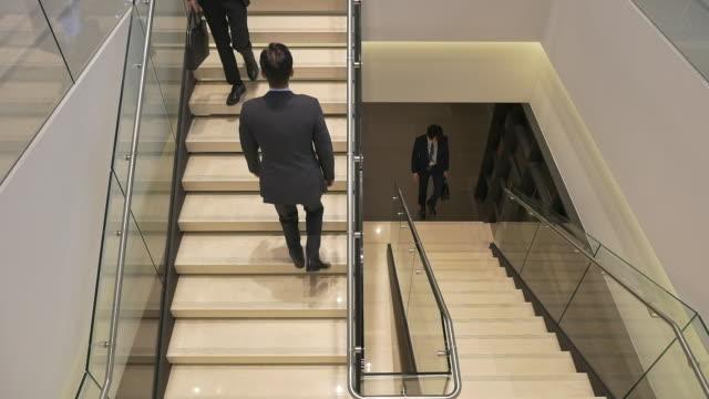 employees walking on the stairs - hemd und krawatte stock-videos und b-roll-filmmaterial