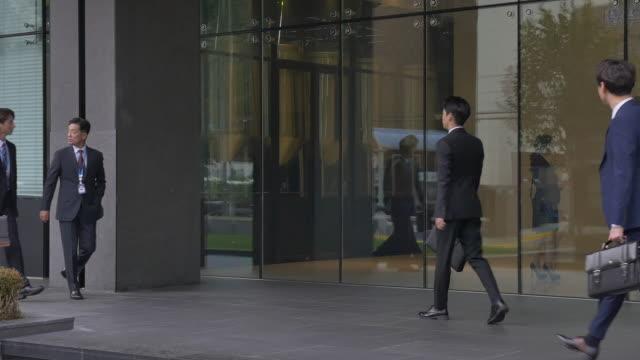 employees walking past an office building - シャツとネクタイ点の映像素材/bロール