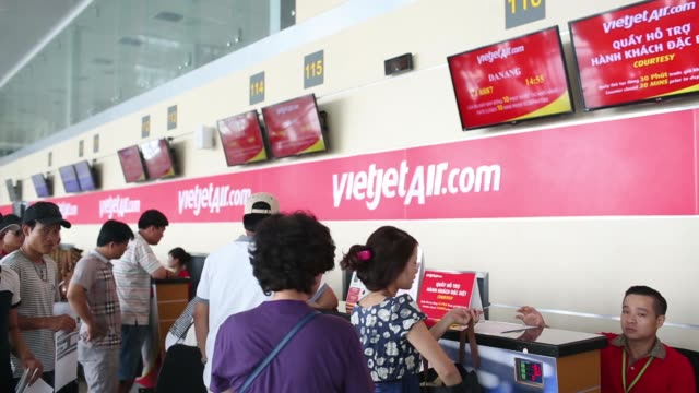employees walks past automated check in machines for vietjet air operated by vietjet aviation joint stock co at noi bai international airport in... - airline check in attendant stock videos and b-roll footage