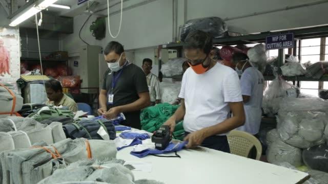 Employees wearing face masks work on the bundling line of a Rajlakshmi Cotton Mills Ltd garment factory in Kolkata West Bengal India on Monday Dec 25...