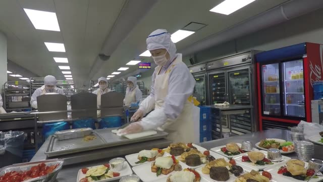 Employees wearing hygiene masks preparing inflight food at the catering facility of Korean Air near Incheon International Airport sometimes referred...