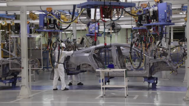 Employees weld parts of Honda Civic vehicles as they work on the production line of the Honda Motor Co assembly plant in Prachinburi Prachinburi...