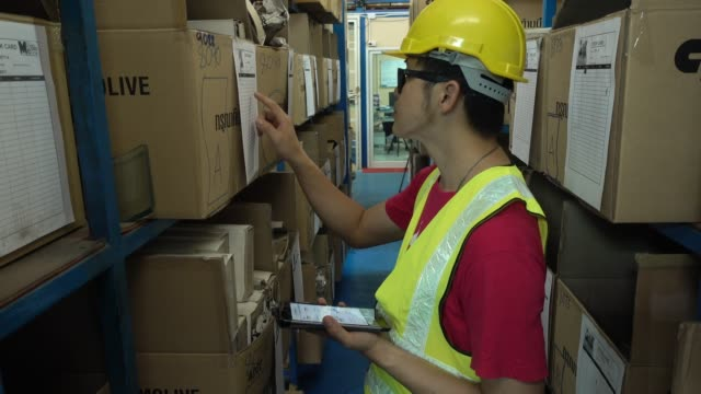 Employees with tablet at logistics in warehouse.