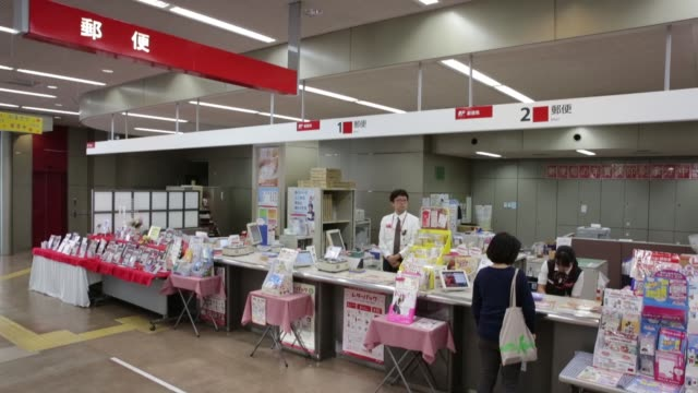 employees work at banking and insurance counters at a japan post co post office in tokyo, japan, on monday, oct 26 signage for japan post co is... - mail点の映像素材/bロール