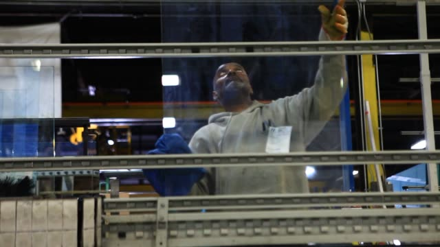 vídeos de stock e filmes b-roll de employees work at the maryland glass and mirror co facility in baltimore maryland us a black male employee wearing a sweatshirt and work gloves... - sweatshirt