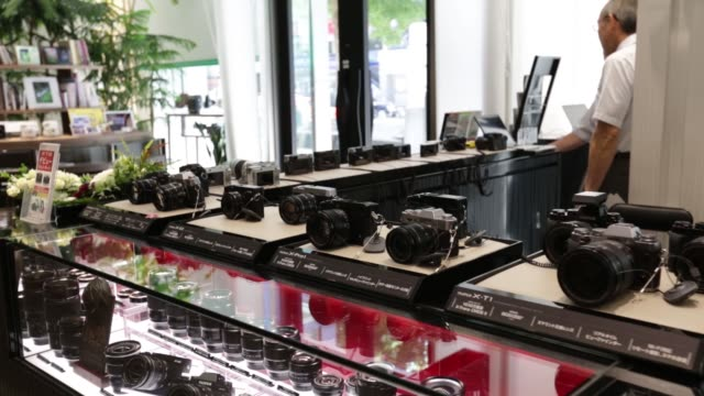 employees work behind a counter at a fujifilm holdings corp digital camera at the companys showroom in tokyo japan on wednesday july 22 various... - digital camera stock videos and b-roll footage
