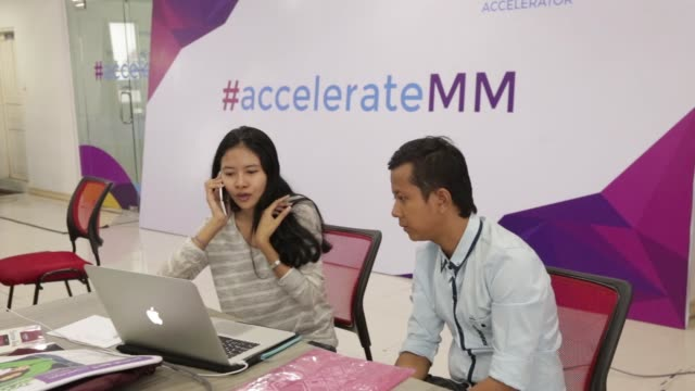Employees work in front of laptop computers at the business incubator Phandeeyar in Yangon Myanmar on Wednesday June 14 An employee uses a mobile...