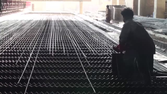 Employees work next to iron rebars sitting on a cooling bed inside an Agha Steel Industries Ltd plant in Karachi Pakistan on Saturday June 3 Iron...
