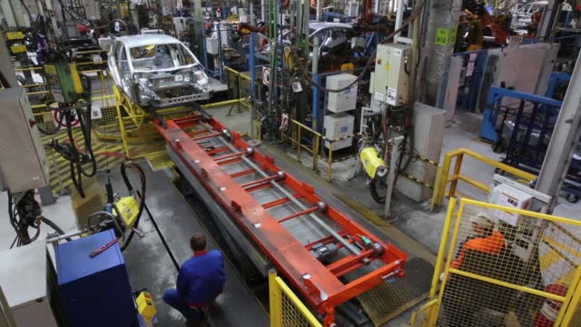 Employees work on a Ford Focus automobile on the production line at the OAO Ford Sollers assembly plant a unit of Ford Motor Co in Saint Petersburg...