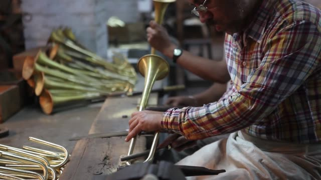 Employees work on bell components of brass instruments in the assembly department of the Nadir Ali Co factory operated by Nadir Ali Wind Instruments...