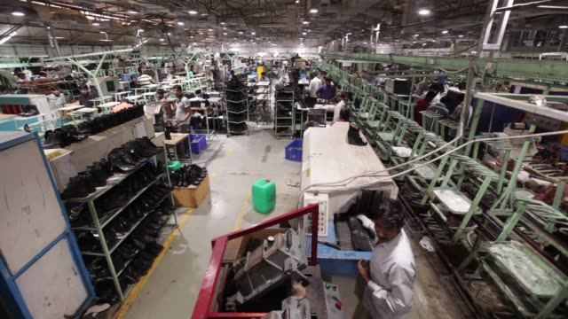 Employees work on the assembly line at a Virola Shoes Pvt manufacturing facility in Agra Uttar Pradesh India on Friday June 23 Pan left to right...