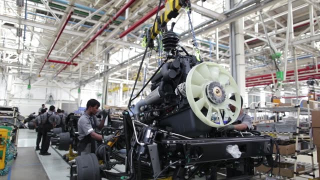 ws employees work on the chassis and powertrain of a bharatbenz truck on the production line employees install the engine of a bharatbenz truck ms an... - fahrgestell stock-videos und b-roll-filmmaterial