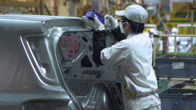 Employees work on the chassis of a Trumpchi brand vehicle on a production line at the Guangzhou Automobile Group Co Ltd plant in Guangzhou China on...
