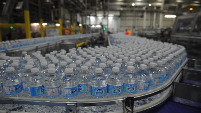 Employees work on the manufacturing floor inside the Nestle Waters Canada plant near Guelph Ontario Filled Nestle Water Bottles cluster together as...