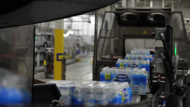 Employees work on the manufacturing floor inside the Nestle Waters Canada plant near Guelph Ontario 24 packs of Nestle Bottled Water move down an...