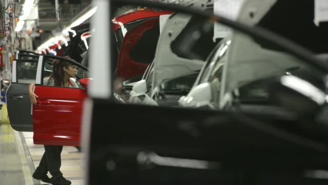 vídeos de stock, filmes e b-roll de employees work on the mechanized production line for the assembly of seat leon vehicles at volkswagen ag's seat automobile plant in martorell spain... - produto interno bruto