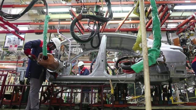 Employees work on the Renault SA Duster sportutility vehicle assembly line at the Renault Nissan Automotive India Pvt manufacturing plant in Chennai...