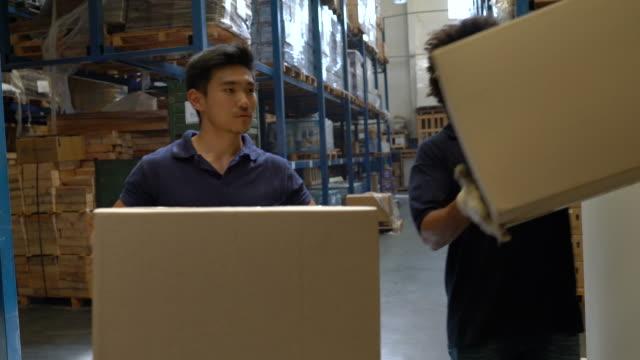mitarbeiter, die in einem großen vertriebsunternehmen arbeiten - distribution warehouse stock-videos und b-roll-filmmaterial