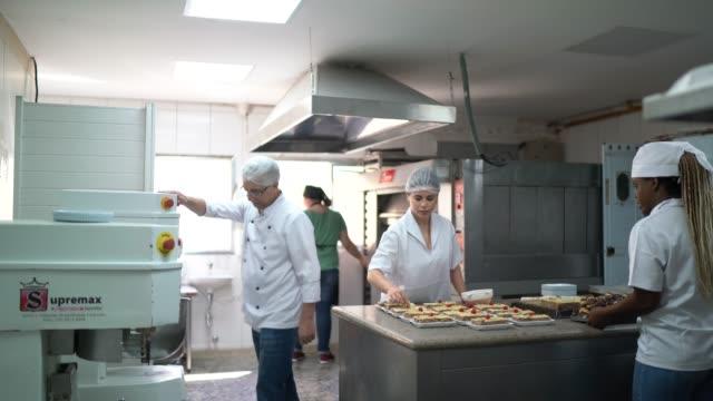 stockvideo's en b-roll-footage met werknemers die desserts in een commerciële keuken bereiden - bakkerij