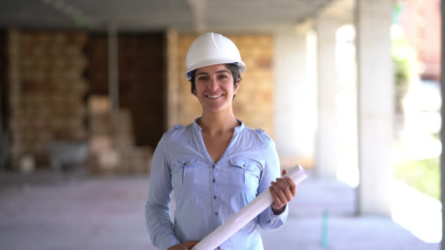 empowered female architect walking towards the camera smiling at it and holding a blueprint - architect stock videos & royalty-free footage