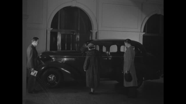 stockvideo's en b-roll-footage met ms empty 1930s sedan / ms man and woman follow car salesman to car he shows them / ms man and woman get into backseat as salesman continues to talk... - passagiersstoel