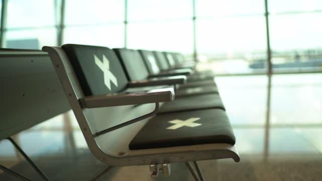 vídeos y material grabado en eventos de stock de sala de espera vacía del aeropuerto con símbolo de distanciamiento social en las sillas - letra x