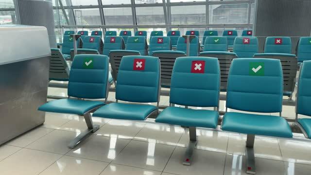 vídeos y material grabado en eventos de stock de sala de espera vacía del aeropuerto con símbolo de distanciamiento social en sillas stock video - letra x