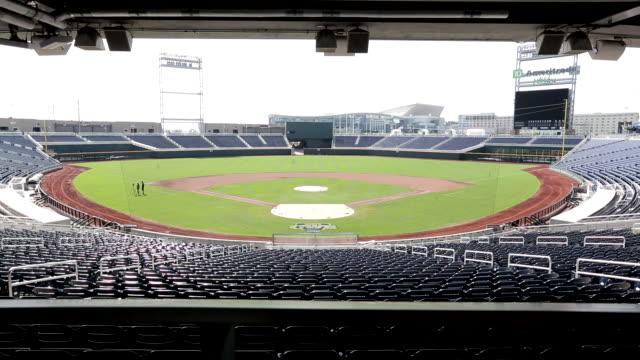 vídeos de stock, filmes e b-roll de empty ameritrade park baseball stadium, rows of blue seats around field, dark electronic scoreboard, overhang top frame, railing fg, centurylink... - paredão rochoso