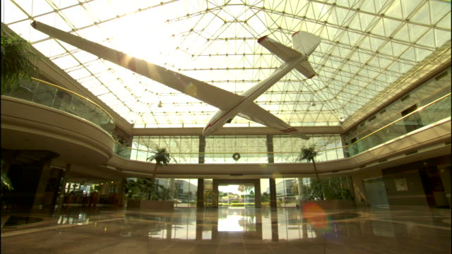 Empty atrium lobby potted palm trees light reflecting on marbal floors large model airplane hanging from glass ceiling sunlight shining through TU/TD...