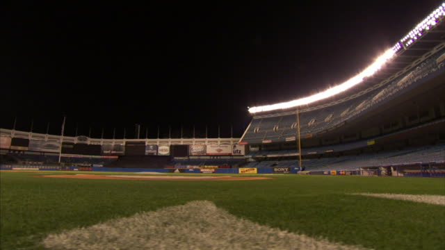 vídeos y material grabado en eventos de stock de empty ballpark dolly behind home plate grass passing yankees ny logo on field behind home plate crane up ws field and tiered seating with baseball... - base home
