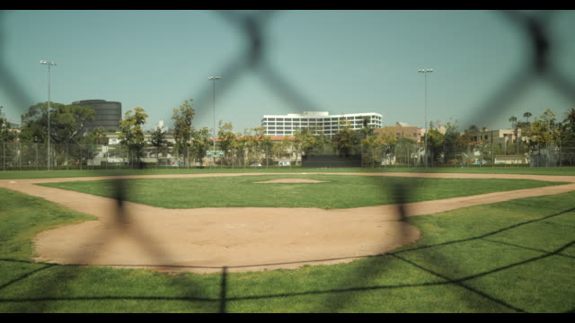 empty baseball diamond shot thru chain link fence, no people, during april 2020 covid-19 - schlechter zustand stock-videos und b-roll-filmmaterial