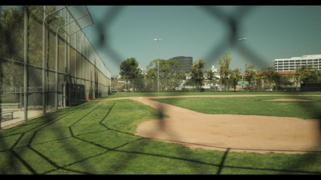 vidéos et rushes de empty baseball diamond shot thru chain link fence, no people, during april 2020 covid-19 - indécision