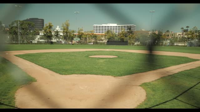 empty baseball diamond shot thru chain link fence, no people, during april 2020 covid-19 - baseball diamond stock videos & royalty-free footage