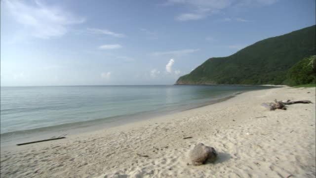 ws pan empty beach and ocean under blue sky, vietnam - seascape stock videos & royalty-free footage