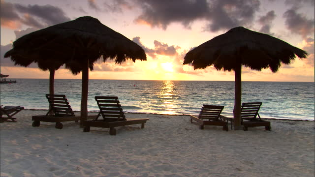 empty beach chairs wait under thatched grass umbrellas on the beach. - mayan riviera stock videos & royalty-free footage