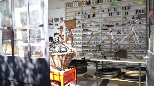 vídeos de stock, filmes e b-roll de loja de bicicletas vazio com duas bicicletas vintage sobre uma mesa e prateleiras cheias de peças de substituição - loja