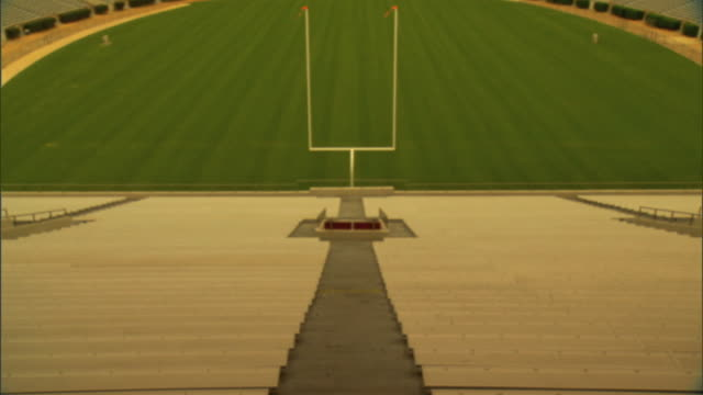 empty bleacher seats end zone unpadded goal post uprights w/ grass turf field bg no people logos or lettering - football goal post stock videos and b-roll footage