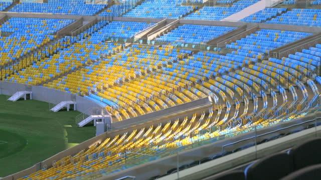 vídeos de stock e filmes b-roll de empty blue and yellow seats in maracana stadium stands - material