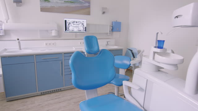 empty blue dentist's chair against medical x-ray - clinica medica video stock e b–roll