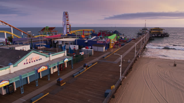 empty boardwalk and closed businesses on santa monica pier during covid-19 lockdown - aerial - city stock videos & royalty-free footage