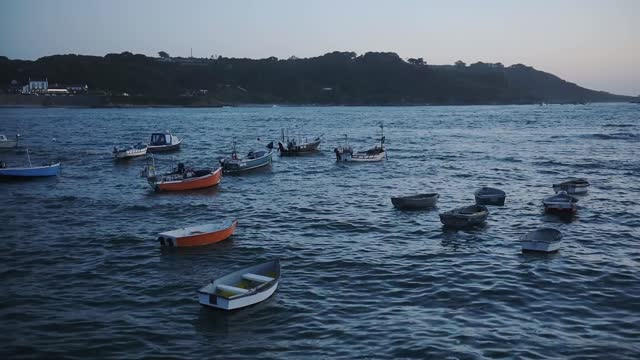 empty boats tied by the shoreline of guernsey during the night - wide shot - anchored stock videos & royalty-free footage