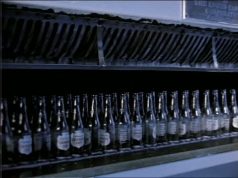 1951 pan empty bottles running by on conveyor belt past man in bottling factory - 1951 stock videos & royalty-free footage