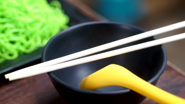 Empty bowl of Asian food with wooden chopsticks and yellow spoon in a restaurant.