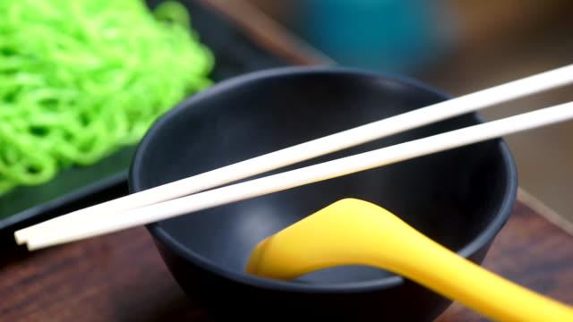 vidéos et rushes de bol vide de nourriture asiatique avec des baguettes en bois et la cuillère jaune dans un restaurant. - bol vide