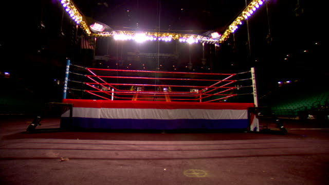empty boxing ring w/ red white blue draping around bottom edge of ring overhead spotlights on dolly up to ring drapes - boxing ring stock videos & royalty-free footage