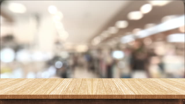 empty brown wood table and blurred people shopping at supermarket light background. mock up backdrop template for product display.promotion stand. - shelf stock videos and b-roll footage