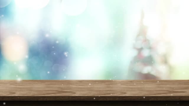 Empty brown wood table and snow falling with blur christmas tree bokeh light background,Backdrop template for display of product or design,food stand mock up.