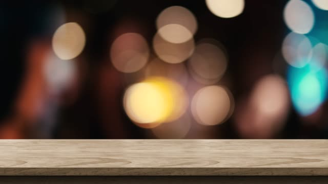 empty brown wood table top with blur night club bar bokeh light background,backdrop template for display of product or design,food stand mock up - ristorante video stock e b–roll